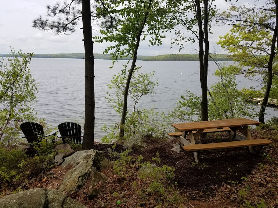 Adirondack chairs and private picnic table setting at water's edge.