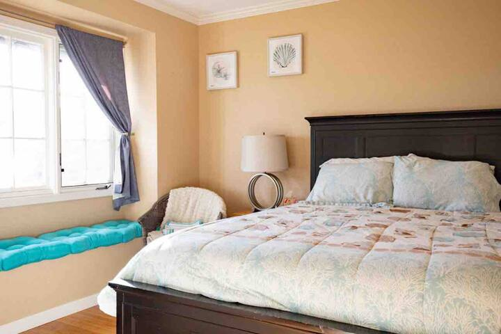 Private bedroom with full bathroom attached. Queen bed with four drawers. Breakfast/Reading nook by gorgeous window with Ocean Breeze