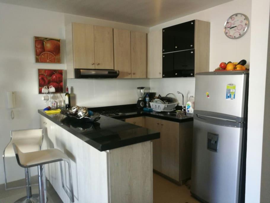 Cocina integral, con nevera, vajilla y utensilios de cocina