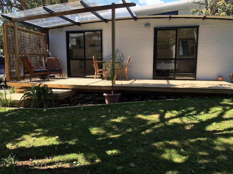 large deck and undercover area with comfortable chairs and table