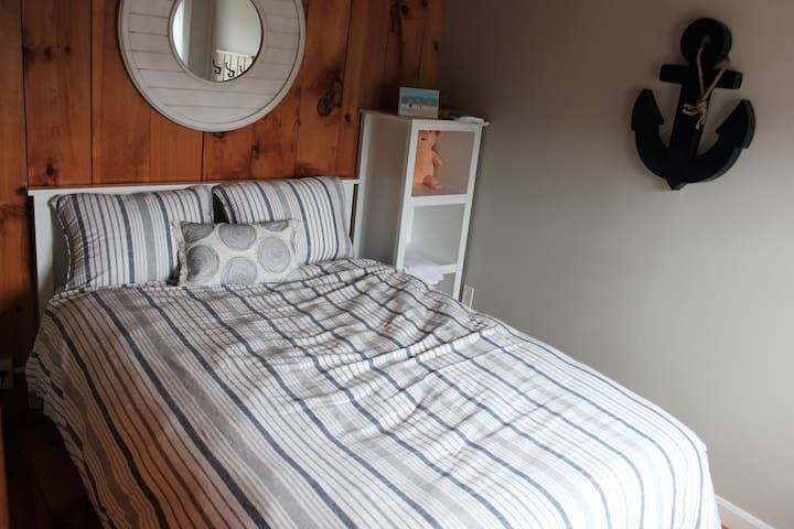 Downstairs Bedroom featuring a full size bed, dresser and closet overlooking the beautiful marsh and tall pine trees.