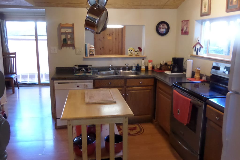 Kitchen with microwave, dishwasher, glass top range and full refrigerator with ice maker.
