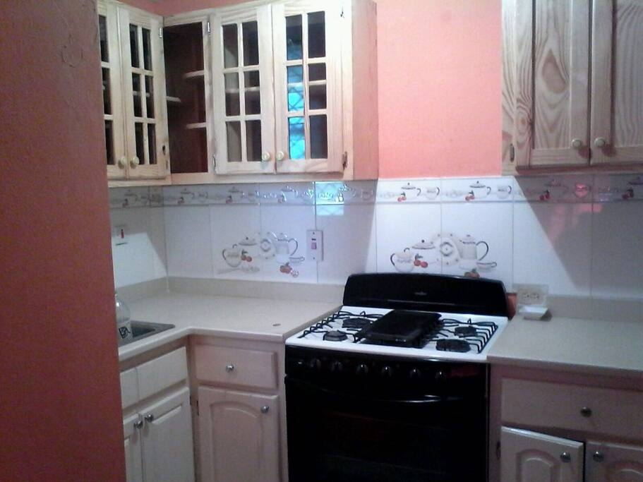 Kitchen with stove and as many cupboards as you can use