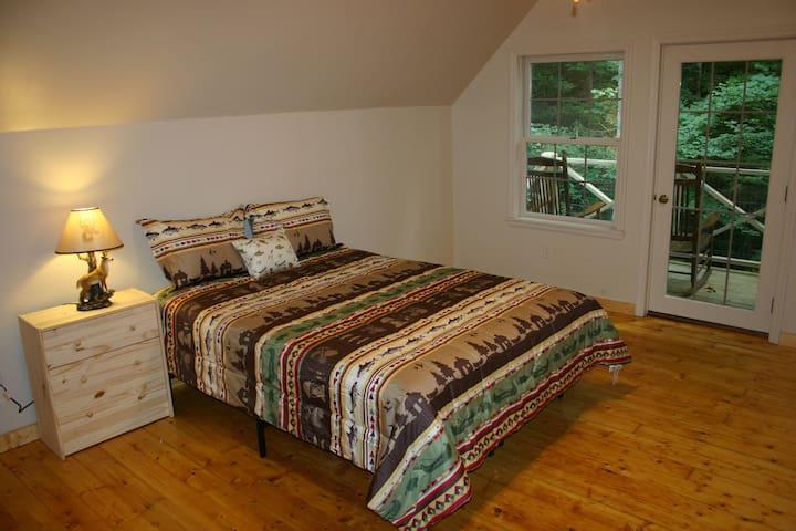 Bedroom 4 with queen bed, HDTV, and rocking chair balcony overlooking creek