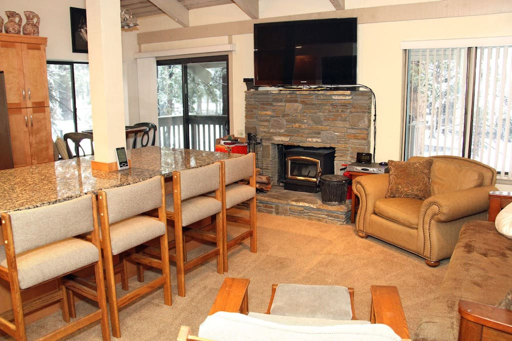 Mammoth Lakes Rental Sunshine Village 148 open concept kitchen and living room with wood stove and access to outside deck