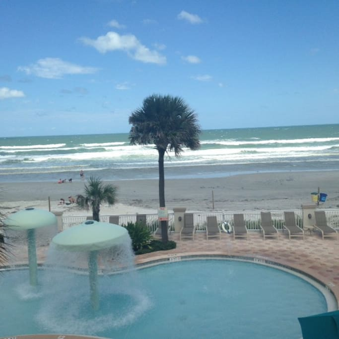 View from condo's private balcony-direct oceanfront with 2 lounge chairs and side table