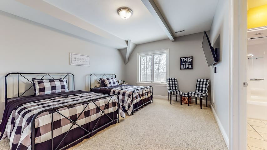 """""""Black and white plaid"""" bedroom with two double beds and 55"""" TV. This bedroom has a full Jack & Jill bathroom that is shared with the """"Blue peony"""" bedroom. Located on the 2nd floor."""