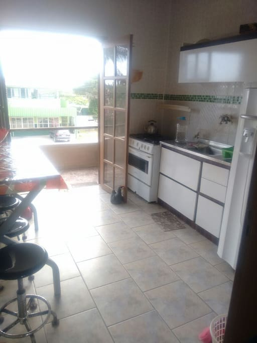 Cozinha com acesso a churrasqueira e varanda com bela vista