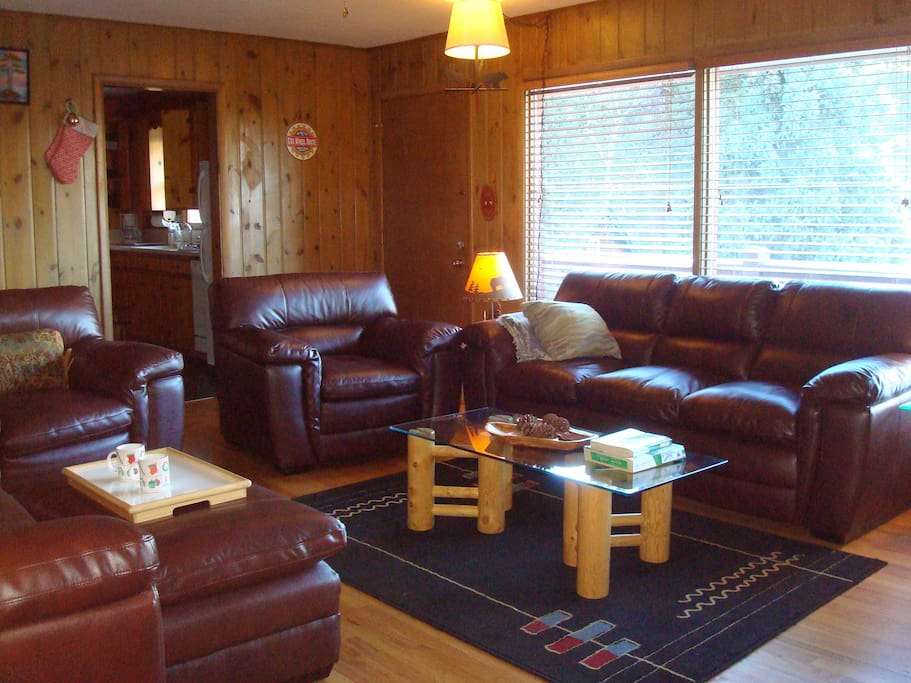 COZY LIVING ROOM HAS 2 SETS OF LEATHER FURNITURE PROVIDING COMFORTABLE SITTING FOR 8 PERSONS