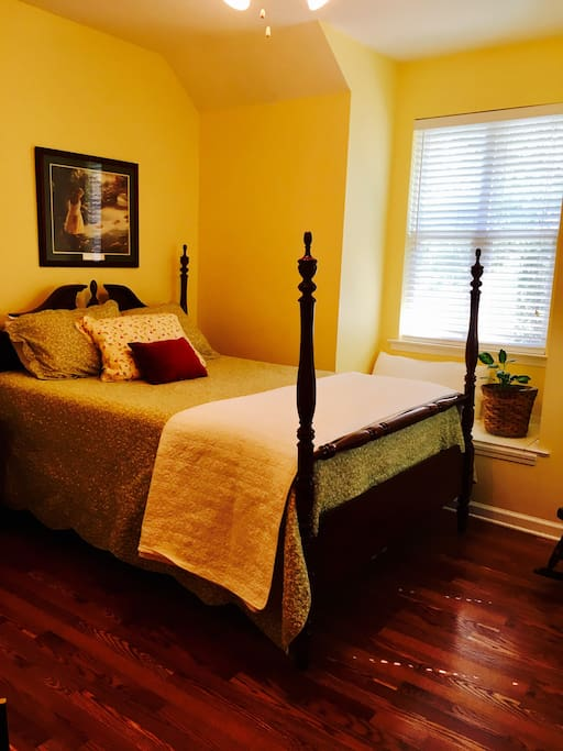 A sunny and inviting upstairs bedroom with a window seat and private bathroom attached.