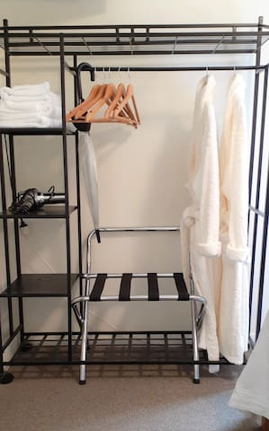 Storage for suitcases and clothes includes, gowns, extra towels and soap, hairdryer and hangers