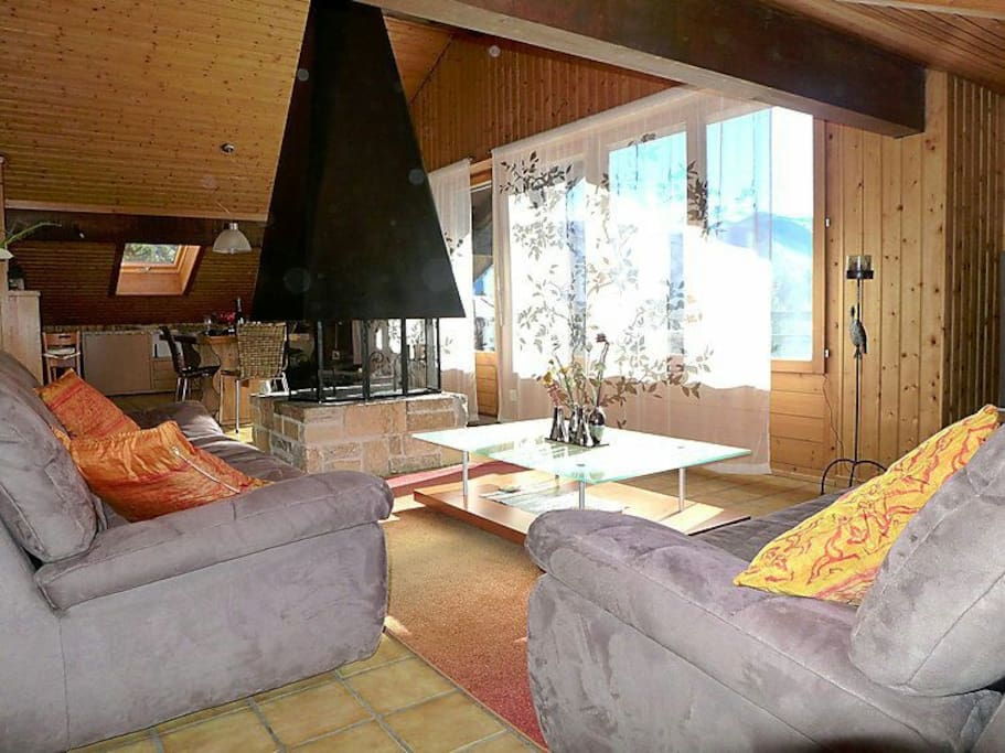 Large living room with fire place, open kitchen and dining area, with a panoramic view onto the forest & lake.