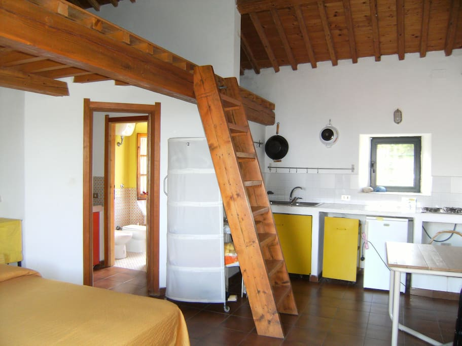 Cucina con tavolo (sulla destra) e vista ingresso del bagno.