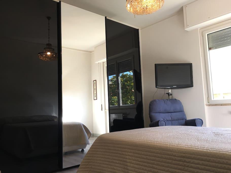 Nella stanza ampio armadio con anta centrale a specchio, televisore con Google chromecast