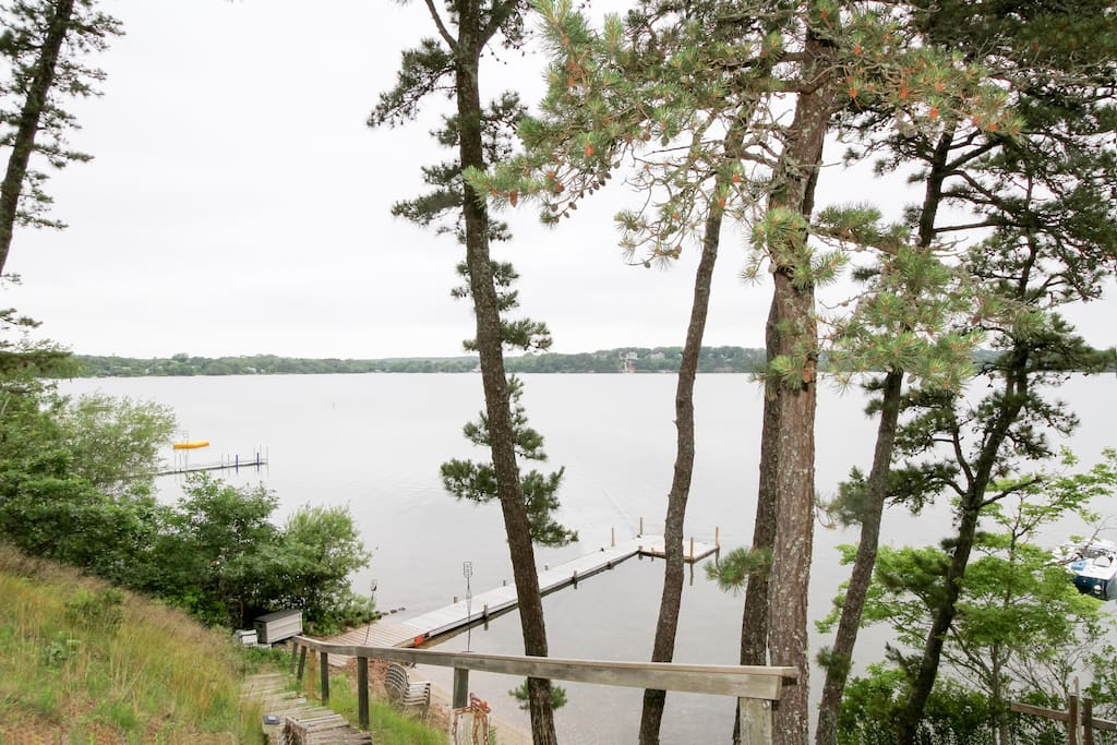 Just steps away, this exclusive home features a private beach and dock on Long Pond.