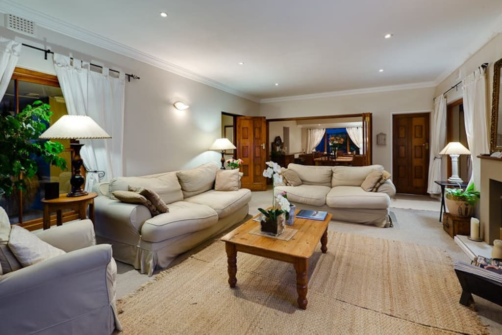 Spacious Lounge area with 55ins TV, DSTV and WiFi leading onto an enclosed covered Patio and Pool with stacking doors.