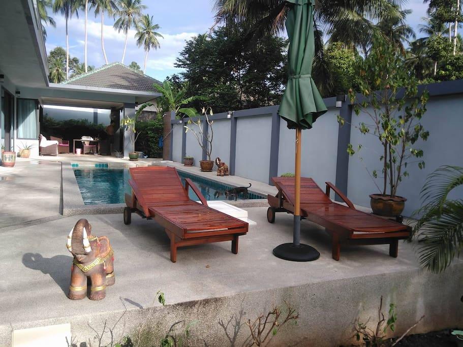 Lit de soleil et parasol sur terrasse.