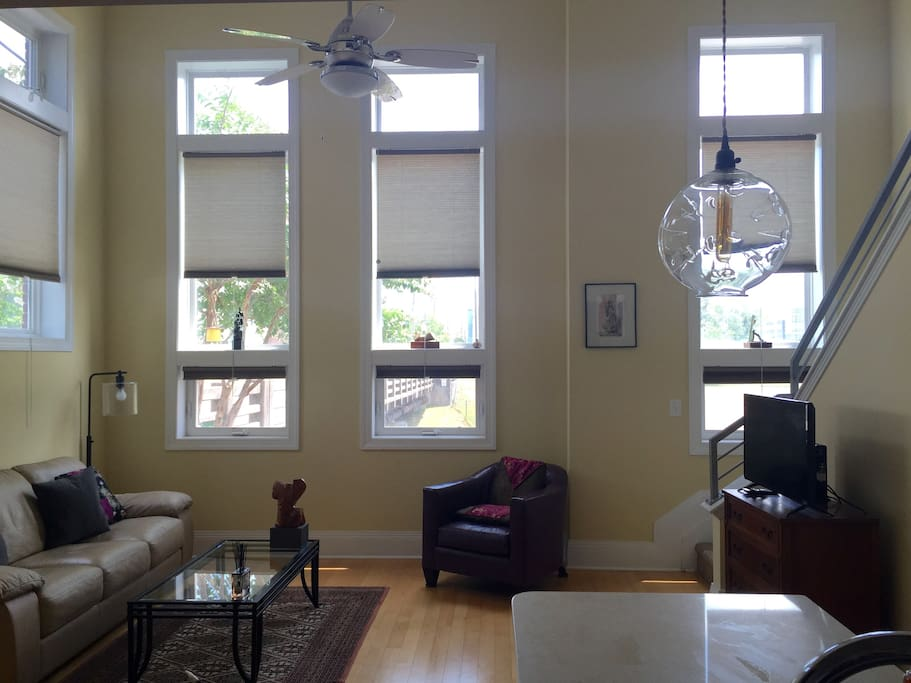 Big tall windos. Comfortable living room. Watch the world go by outside your windows, or not!  Full window curtains.