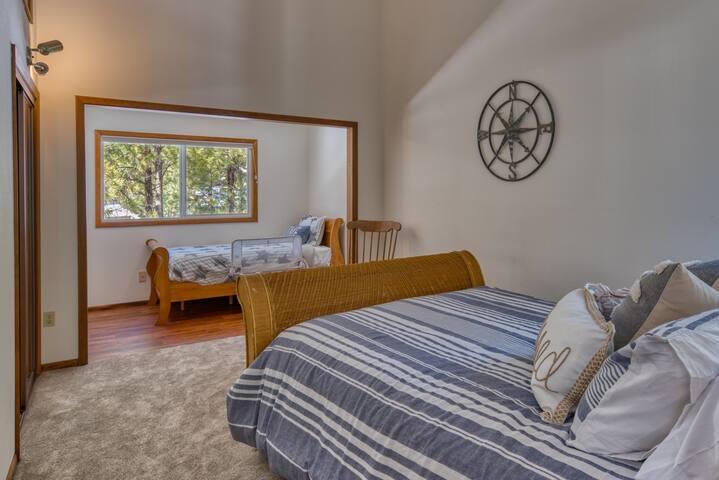 Upstairs left bedroom (queen and single beds)