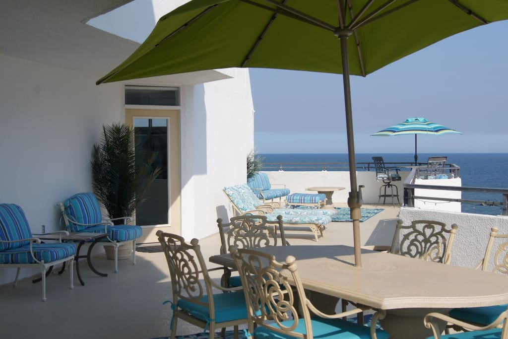 Large private balcony with plenty of seating, umbrella's and lights to enjoy the ocean and bay views.