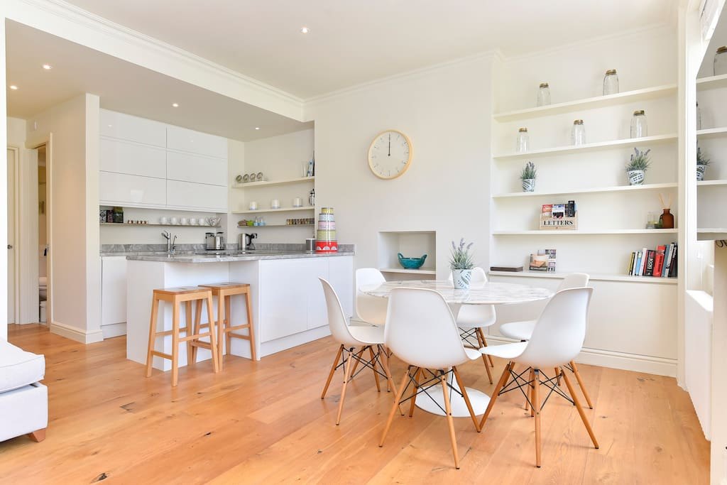 The open plan dinning/living/kitchen area is bright light and spacious. It has a table and breakfast bar.