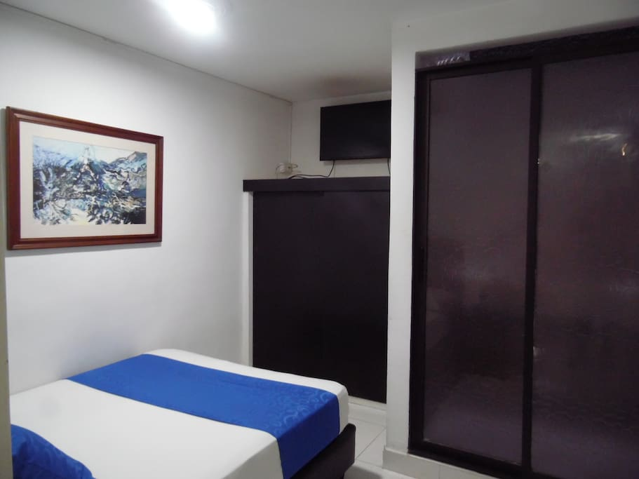 Alcoba con cama doble y televisor. Main room with a double bed and television.