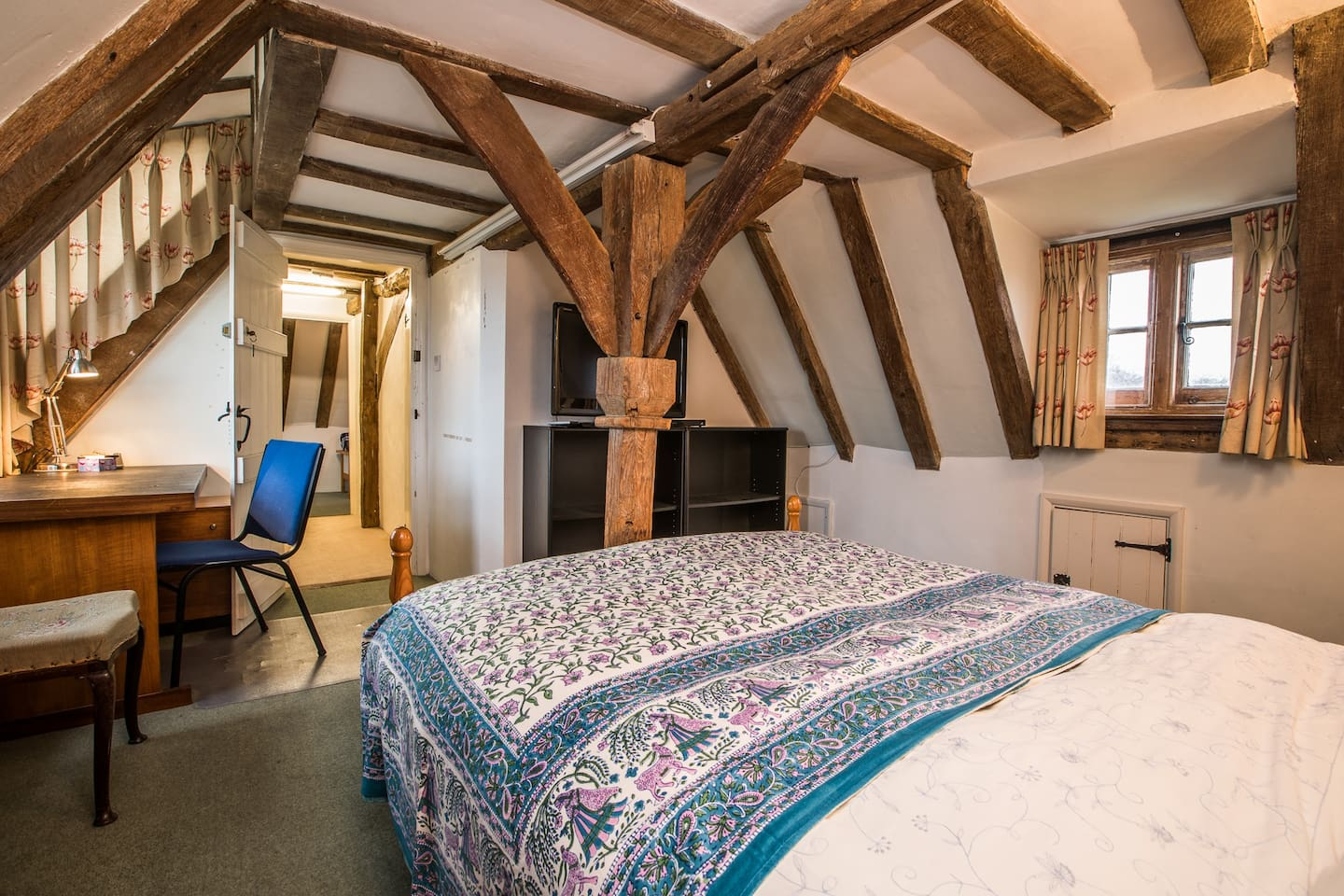 The bedroom with the historic 'king post' of the house; it dates from about 1500 and is a typical feature of timber framed houses in the region.