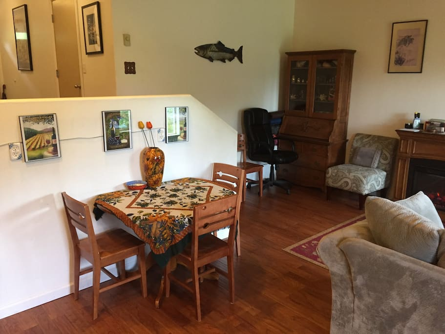 Kitchen table with wine pictures above it and metal salmon on wall