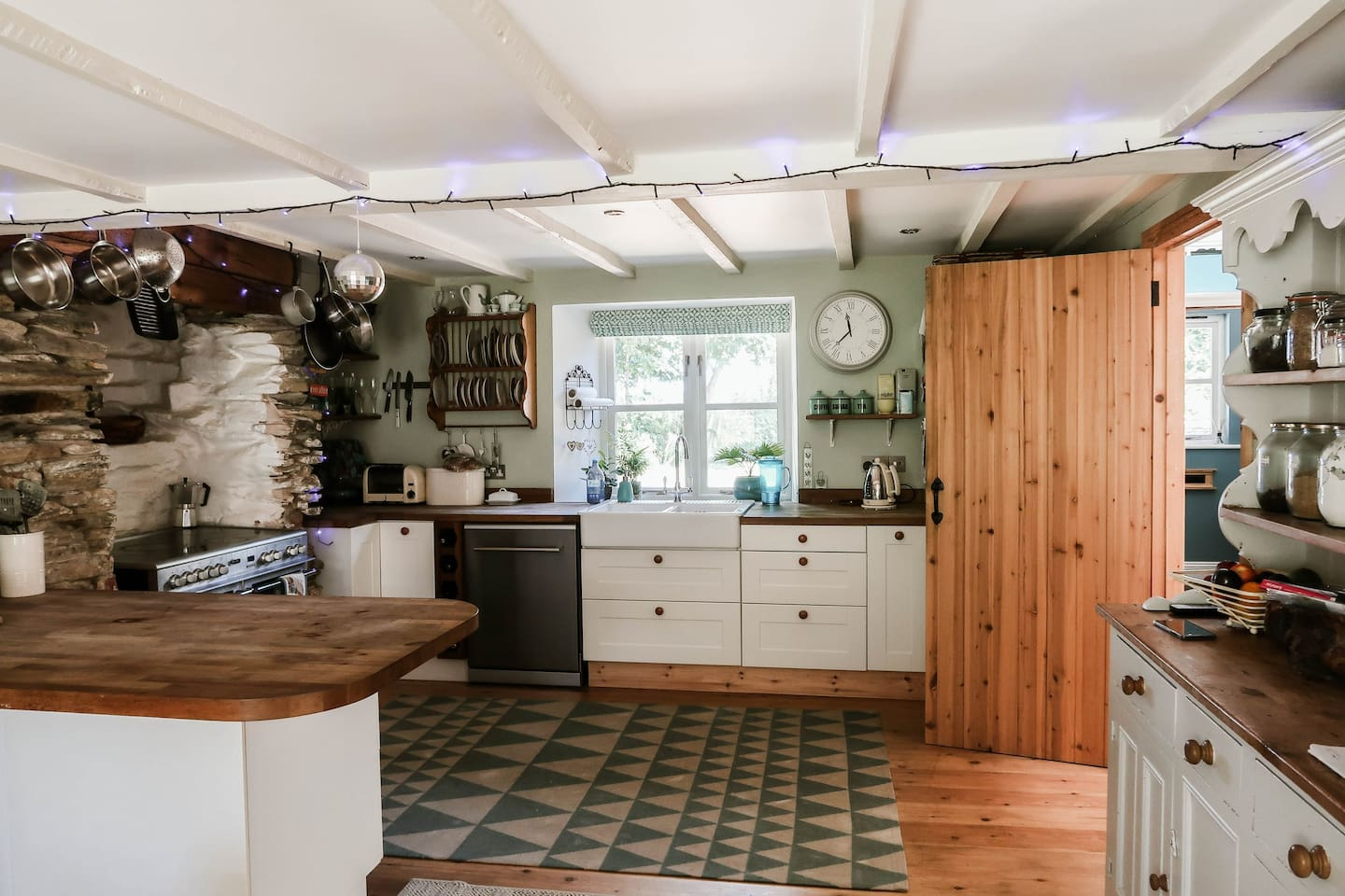 Fully fitted kitchen with breakfast bar, double farmhouse sink, range oven, dishwasher and stone pillar features.