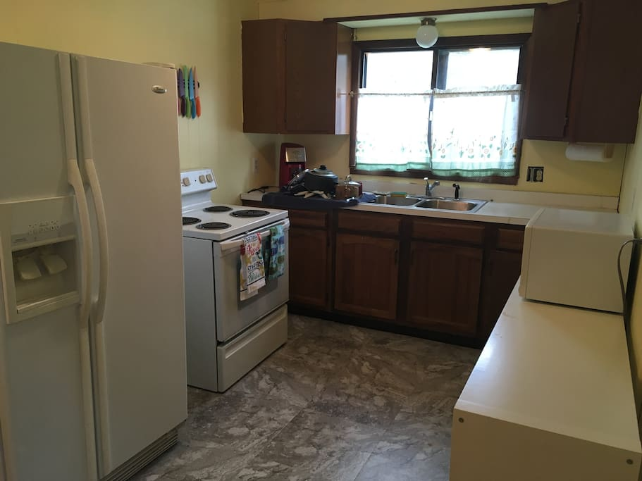 Kitchen with new flooring, fridge, microwave, stove, & coffeemaker