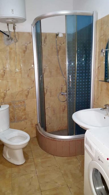 Bathroom with a shower, a toilet and a washing machine