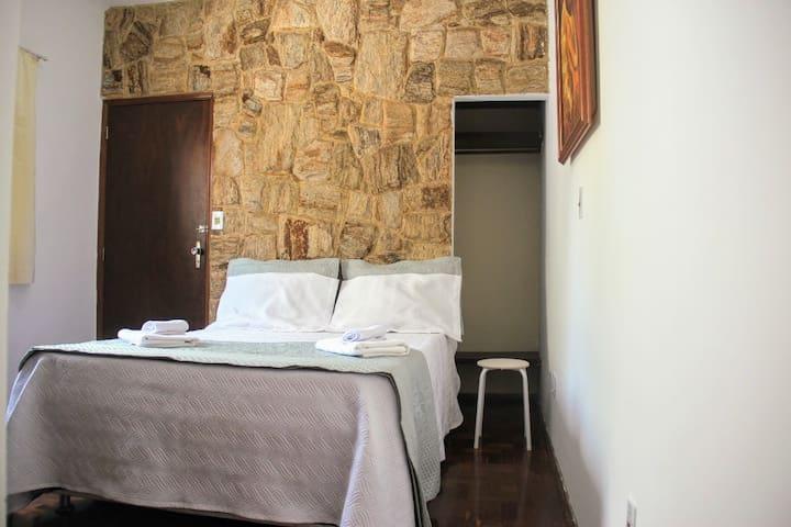 Quarto suite com cama de casal, armário embutido e closet