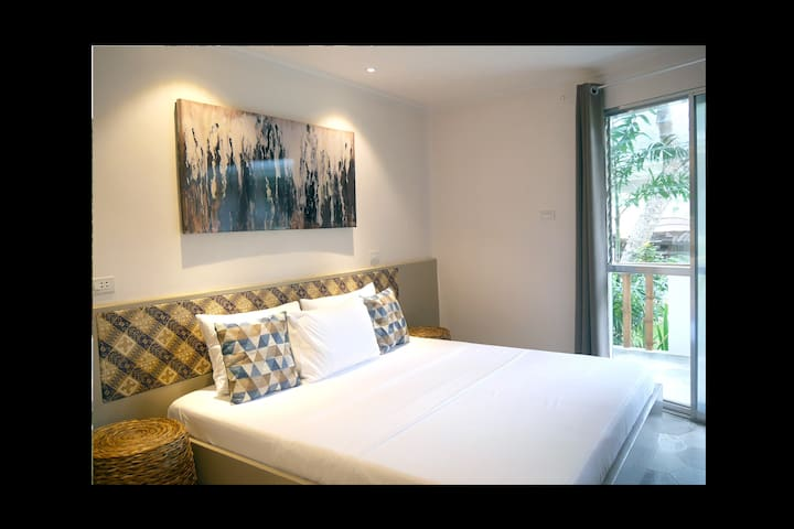 Master bedroom with king-size bed and private balcony