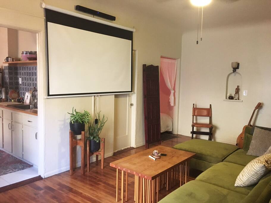 sun-filled relaxing living space with pull down projector screen and sound bar for movies!