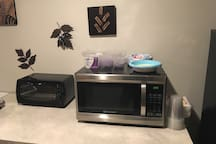 The mini-kitchen area includes a microwave and small counter oven with disposal plates, dishes, cups, and utensils. There is no dedicated kitchen sink in the basement. Washing of pots is available with permission in the upstairs kitchen.