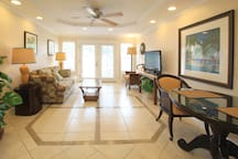 Living room features tiled floors, air conditioner, dinette set, sofabed, flat screen TV with DVD player, and ceiling fan