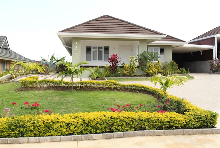 3 bedroom, 2 bath bungalow sits on top of the hill allowing a breath taking view of both the hill and the sparkling blue Caribbean Sea.  Driveway provides ample parking for up to 5 cars.  The house is surrounded by luscious well manicured landscape.
