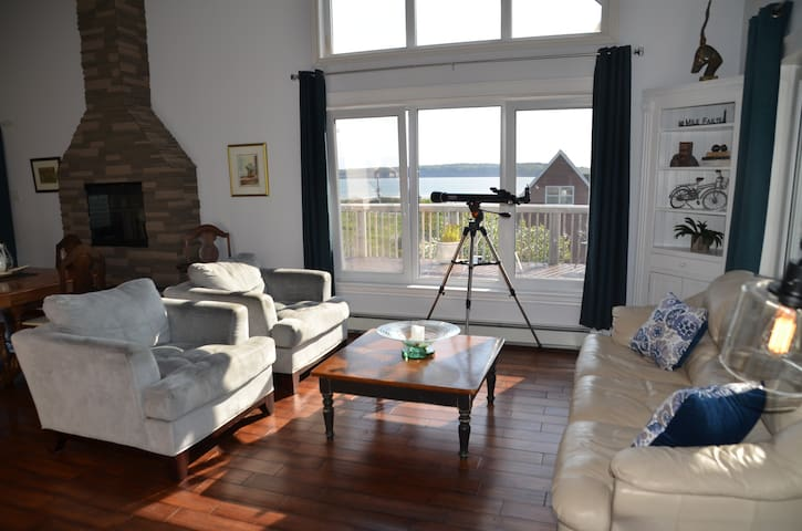 Living Room with expansive windows and ample seating to gather and enjoy the surroundings and changing beauty of the Atlantic ocean throughout the day no matter the season!