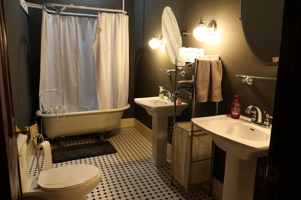 Elegant private bathroom with two sinks & antique tub with shower capabilities!