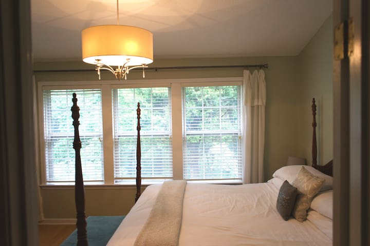3-grand windows in guest suite lend natural light & stunning view of wooded backyard