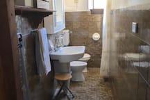 Simple salle de bain avec la douche dans le renfoncement à droite.