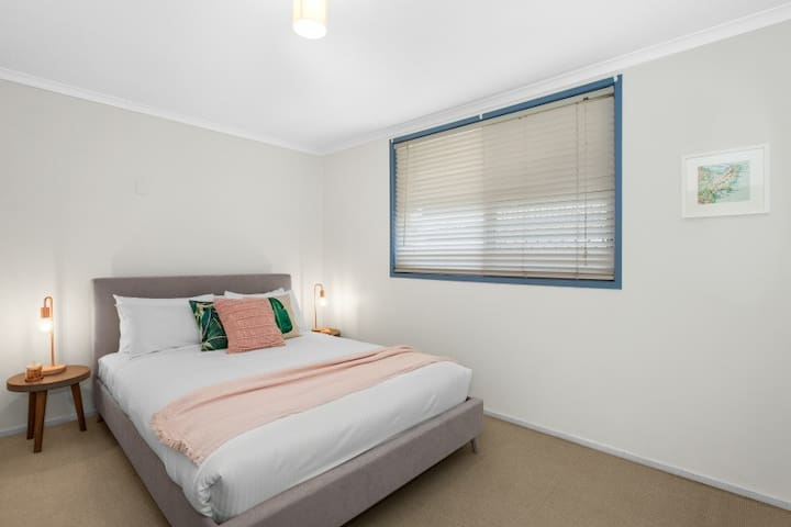 The second bedroom has light streaming in from the window and also offers a queen bed, perfect for another couple or the kids