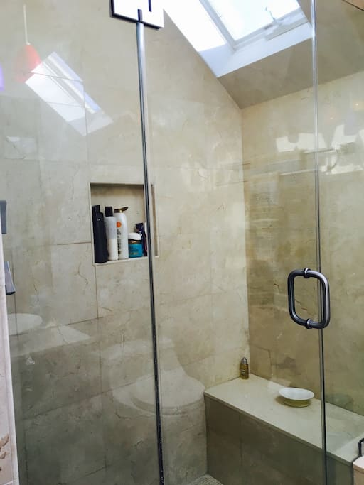 Shower with bench and multiple sprays.