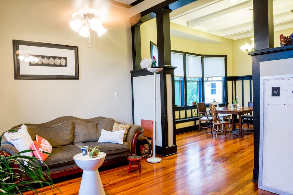 Open-plan living room and dining room bathed in natural light, with high ceilings and original hardwood floors. The perfect spot to kick back.