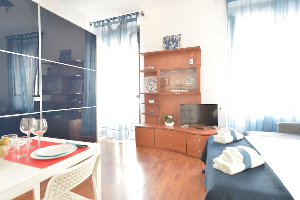 a studio falt with a comfortable bed, spacious wardrobe and a dining area