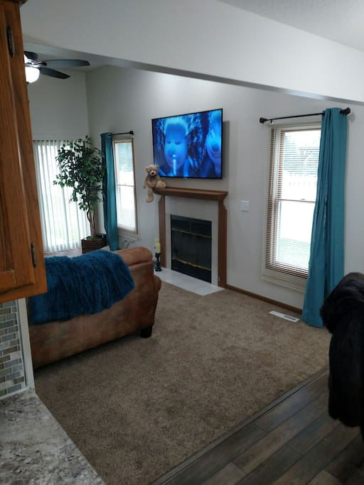 relax in the living room with a 65 inch Smart TV and sliding doors out to the covered patio