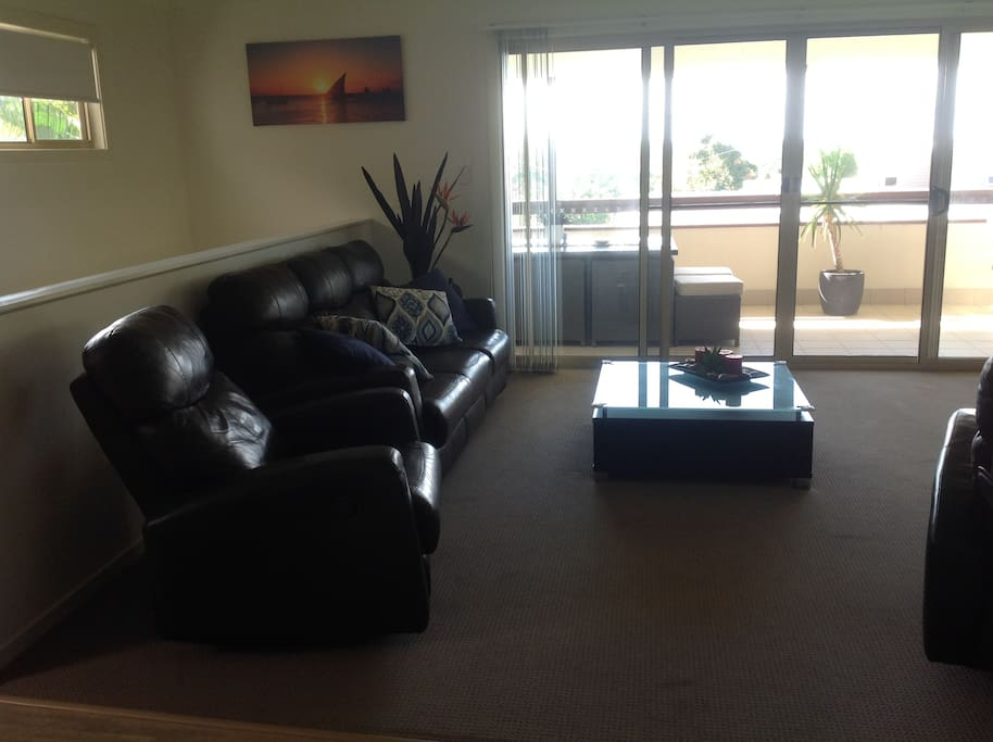 lounge area with 3 seater and 2 recliner leather lounges