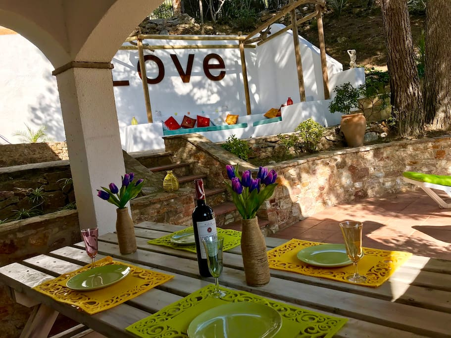 Outside table in front of the pool and the garden