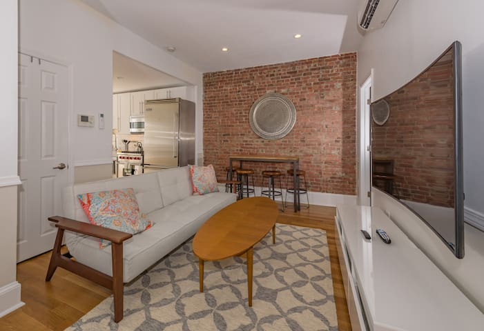 This third-story flat has charming exposed brick, honey-colored hardwood floors and a soothing tan, coral and aqua color scheme.