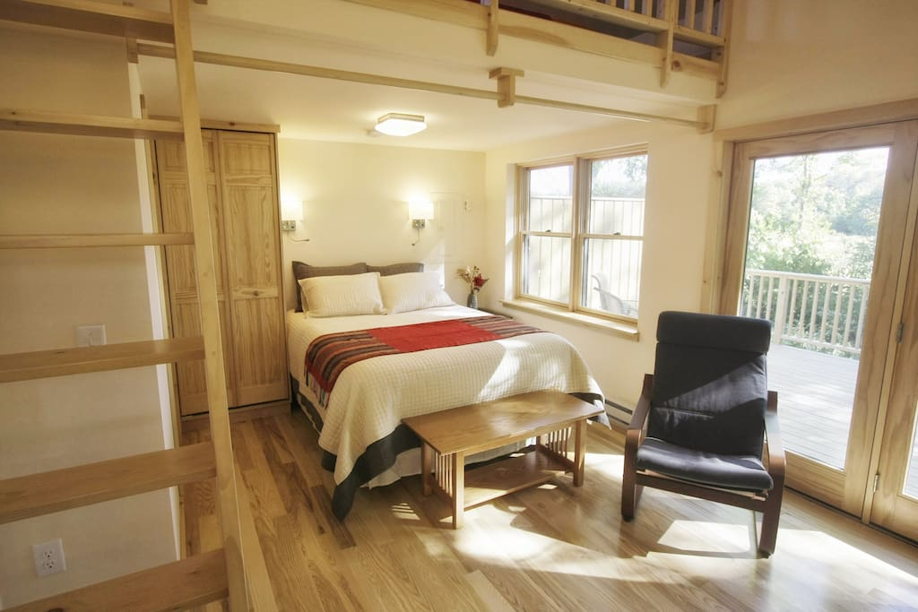 Luxurious queen bed is nestled under the loft area, with closet and bathroom to the left.